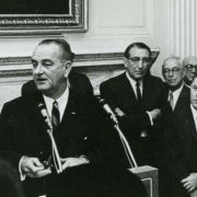 Max M. Fisher looks on as President Lyndon B. Johnson speaks at the White House.