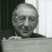 Max Fisher poses with a plaque from an article from The Detroit News about his involvement with the renaissance of Detroit.