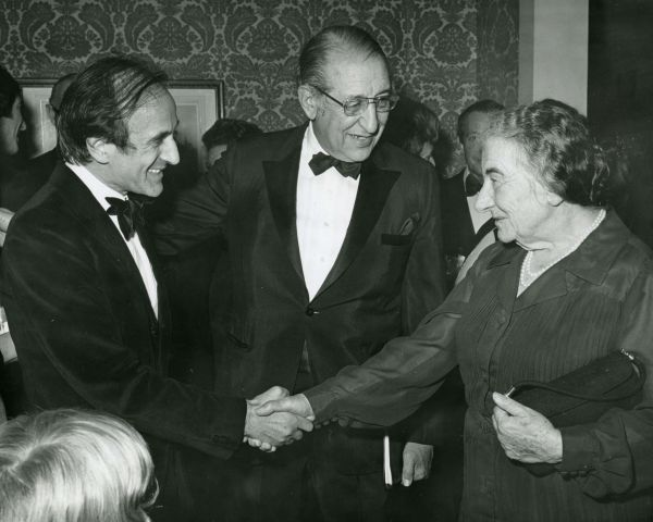 Elie Weisel, Max Fisher and Golda Meir shaking hands.